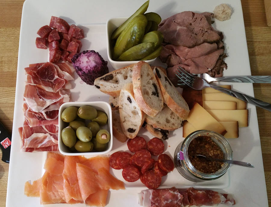 plate with cured meat, cheese, and pickles